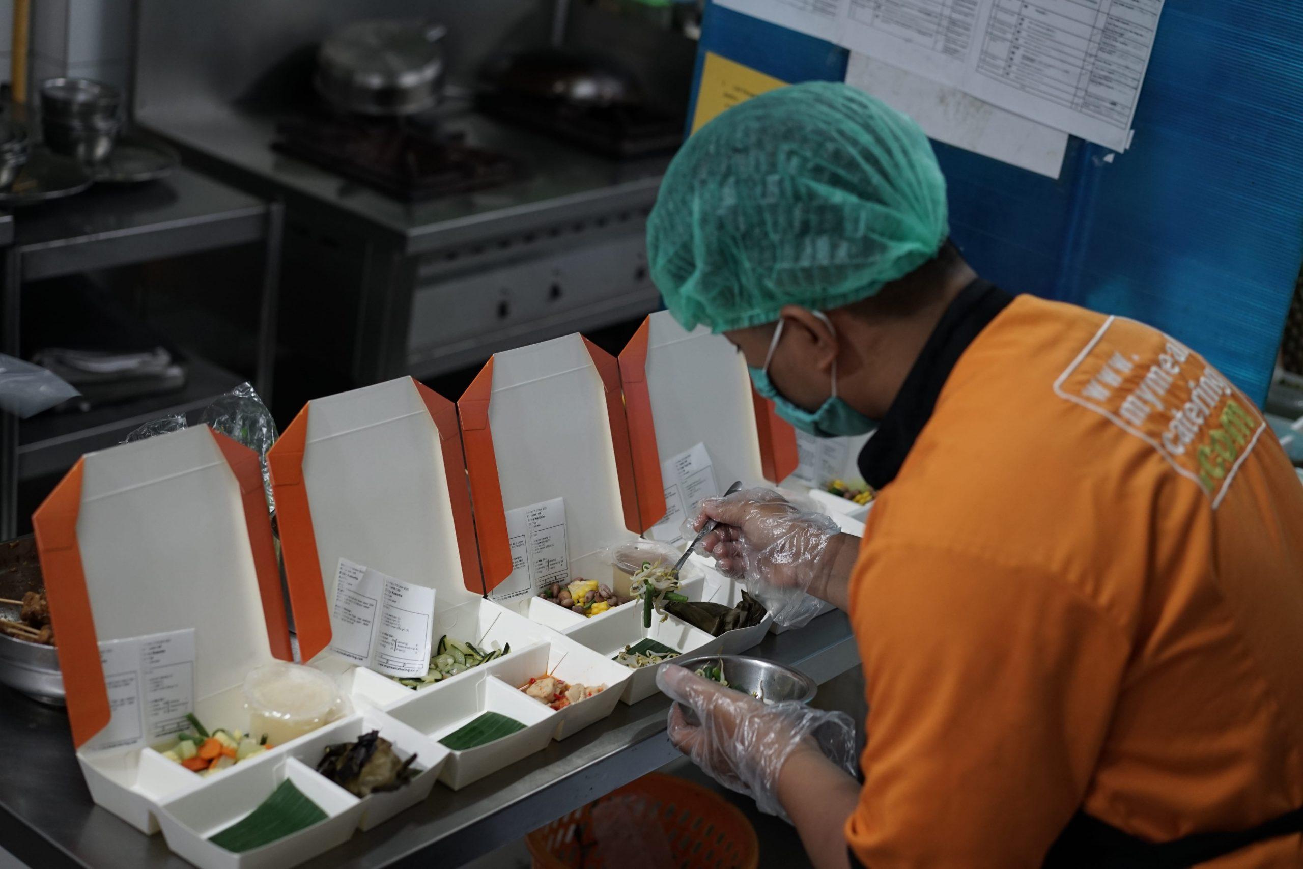 ahli gizi QC MyMeal Catering sedang menata makanan pelanggan